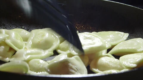 Cooking perogi dumplings in frying pan on stovetop oven Footage