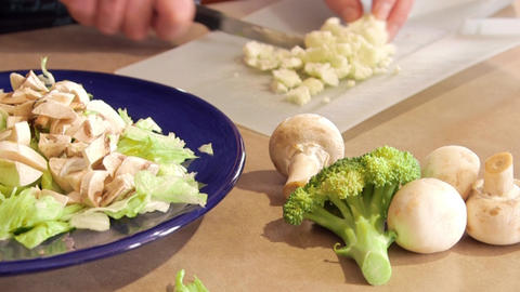 Man preparing dinner salad cutting lettuce and fresh vegetables with a knife Footage