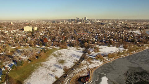 Aerial drone fly downtown city skyline winter snow dusted residential area Footage