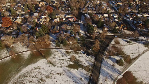 Aerial drone tilt up from snowy winter park to glowing downtown city skyline Footage
