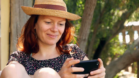 Woman relaxes in the garden enjoying her smartphone in the sun Footage