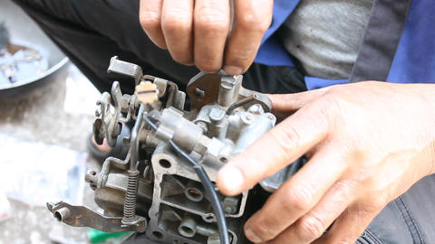 Auto Mechanic or Car Mechanic Tight Carburetor Screw in Car Repair Shop Live Action