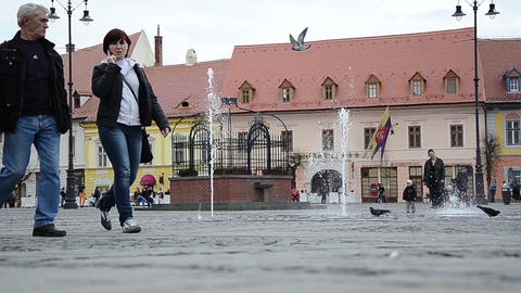 Adults, children and pigeons are here to walk in the central square of a city Footage