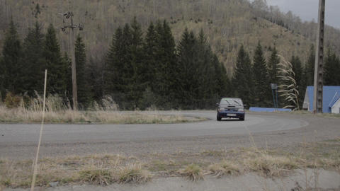 Black car rally takes a tight curve on a gloomy weather and rain bringer 1846f Footage