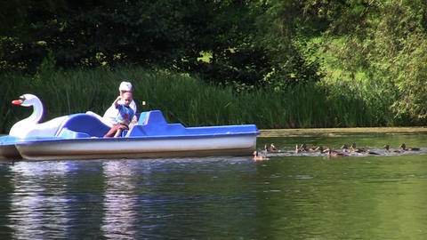 Child and grandfather are boating on the lake and feed the ducks 01 Footage