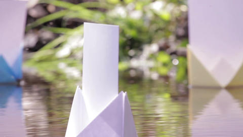 Colored paper boats floating on the muddy water of a creek 81a Footage