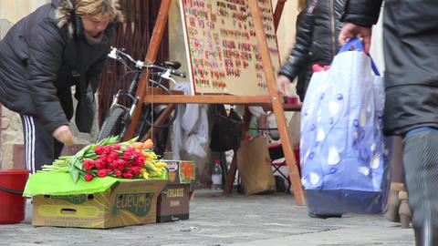 Saleswoman who sells flowers and trinkets stands exposed in the downtown market  Footage