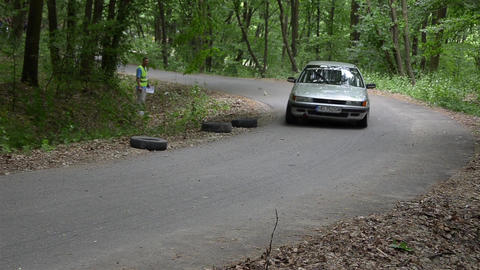 Silver rally car passes a checkpoint in the wood 7003 Footage