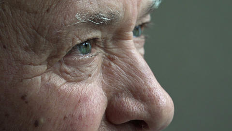 elderly man: old thoughtful man's look: senior man closeup portrait Live Action