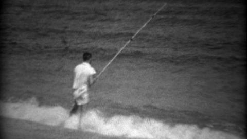 1936: Kid Beach Shore Fishing On Gulf Bay Waters With Long Pole stock footage