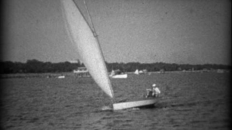 1934: Small sailboat taking 2 passengers across the gentle bay waters Footage