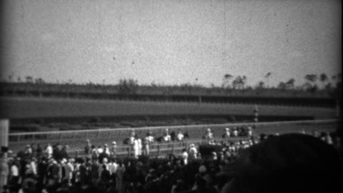 1935: Crowd at horse track race watching horses come out to compete Footage
