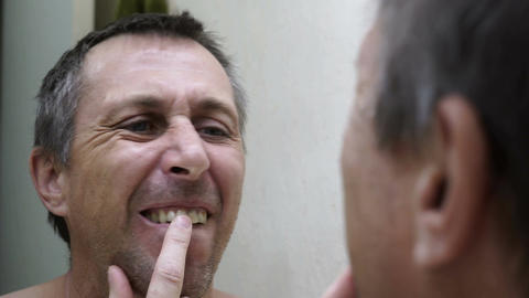 Man Looking into Mirror Inspecting Teeth Handheld Footage