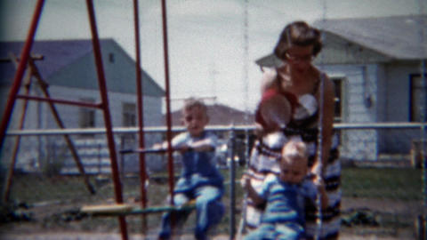 1957: Mom plays kids swingset backyard residential blue house Footage