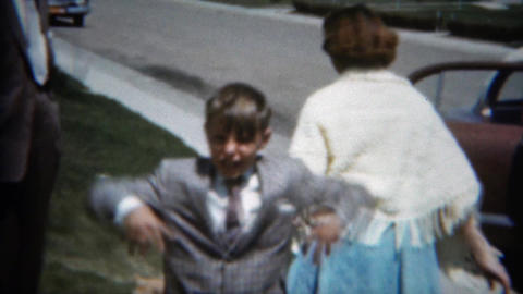 1957: Playful mother in formally dressed family entering suburban parked car Footage