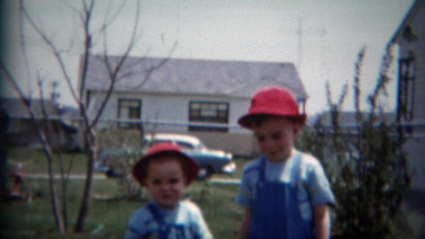 1957: Boy brothers red Swiss alpine hats blue overalls backyard play fun times Footage