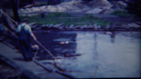 1949: Lumber Mill feeding logs into the conveyer belt milling factory Footage