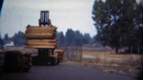 1949: Modern yellow forklift slowly moving lumber woodpile Footage