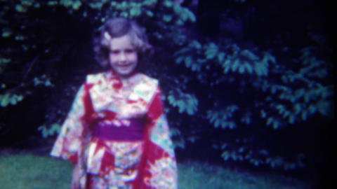 1949: Little Caucasian Girl In Eastern Asian Kimono Style Winged Dress stock footage