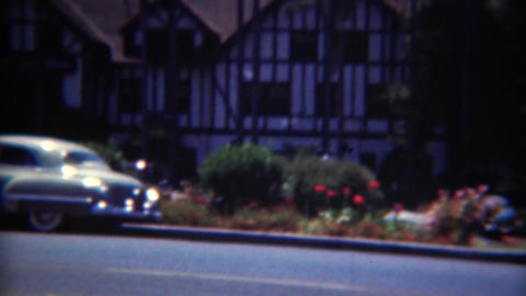 1949: Parked cars on the road in front of tudor architecture style mansion house Footage