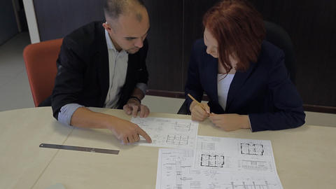 male and female professionals working together on a blueprint house schemes Footage