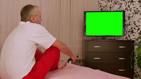 Man watching TV with green screen Footage