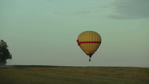 Hot air balloon flying over field in countryside Footage