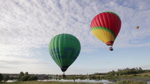 Hot air balloons flying over lake and field Footage