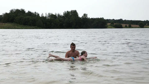 Man teaching girl how to swim Footage