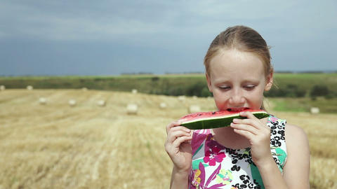 Girl in a field eating watermelon Footage