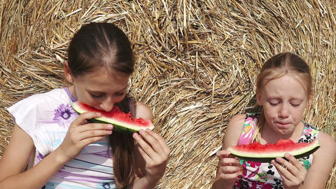 Two girls eating watermelon near the haystack Footage