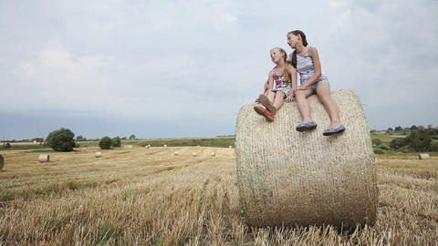 Two girl sits on haystack Footage
