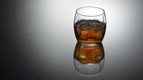 Pouring whiskey into glass with ice cubes Footage