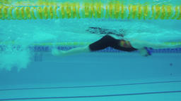 Female swimmer swims in pool 4k video. Underwater view from the water Footage