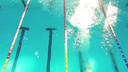 Flight over swimmer jumps off starting block into pool water HD top view video Footage