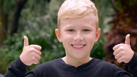 A cute young boy gives two thumbs up, then a third thumbs up comes into frame wh Footage