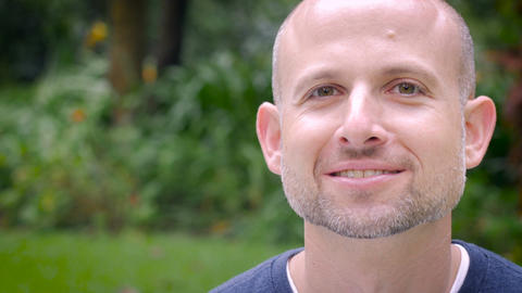 A bald handsome man with a scruffy beard smiles for the camera outside in a park Footage