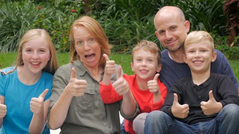 An entire family of 5 give the camera thumbs up and smile outside during the day Footage