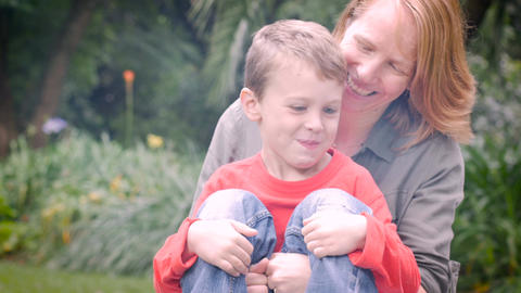A red haired mother holds her young cute son and kisses him with lens flare Footage