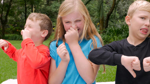Three young children say yuck and hold their noses in disgust as if something sm Live Action