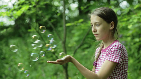 Young girl catches soap bubbles in the park Footage