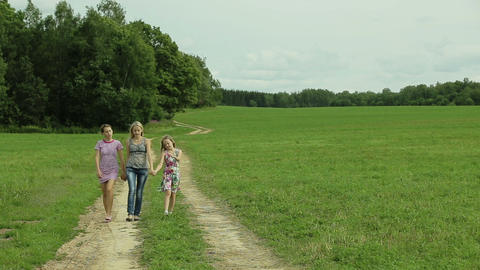 mother and daughters walking holding their hands Footage