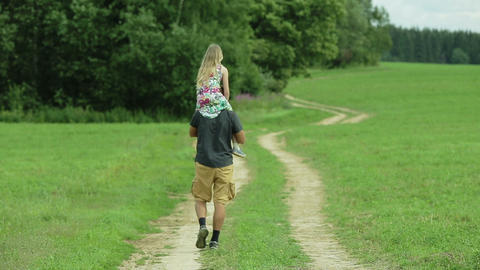 father walking road daughter sitting on his neck Footage