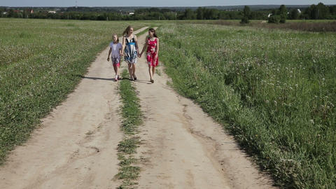 Mother with daughters walk on rural road to field Footage