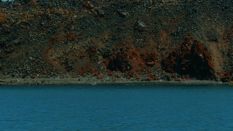 Boat Cruising Approaching A Volcanic Desert Island stock footage