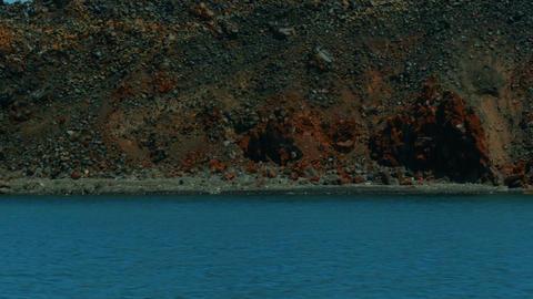 Boat Cruising Approaching A Volcanic Desert Island stock footage