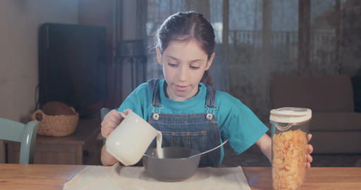 Young girl eating a bowl of cereals with milk Footage