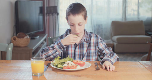 Young boy eating healthy food and vegetables Live Action