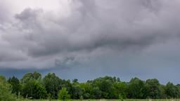 Time lapse of storm clouds passing over green forest Filmmaterial