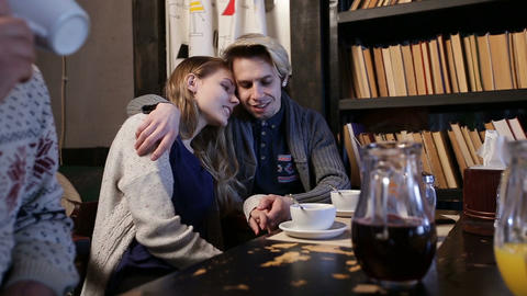 Attractive teenage couple in love in cafe hugging Footage